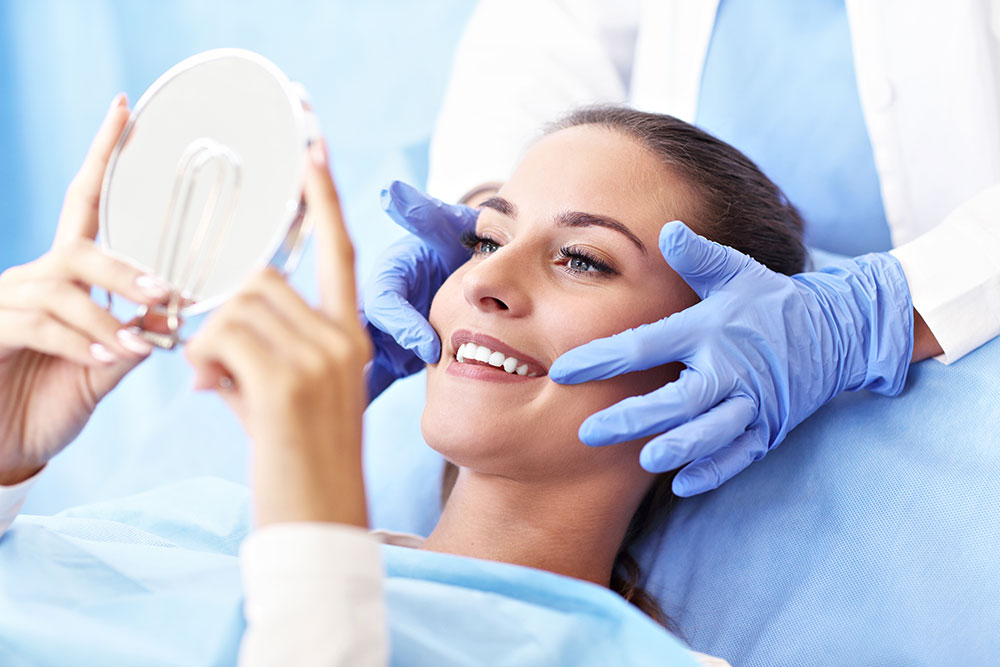 cosmetic dentist showing lady smile in mirror